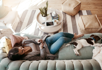 Woman on her couch with her dog while her smart thermostat saves her money and energy