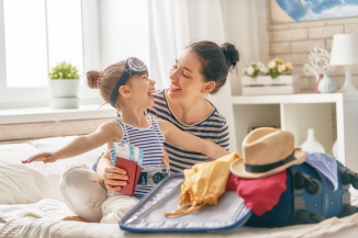 Mother and daughter pack for a trip knowing they can adjust their smart thermostat from a smart phone